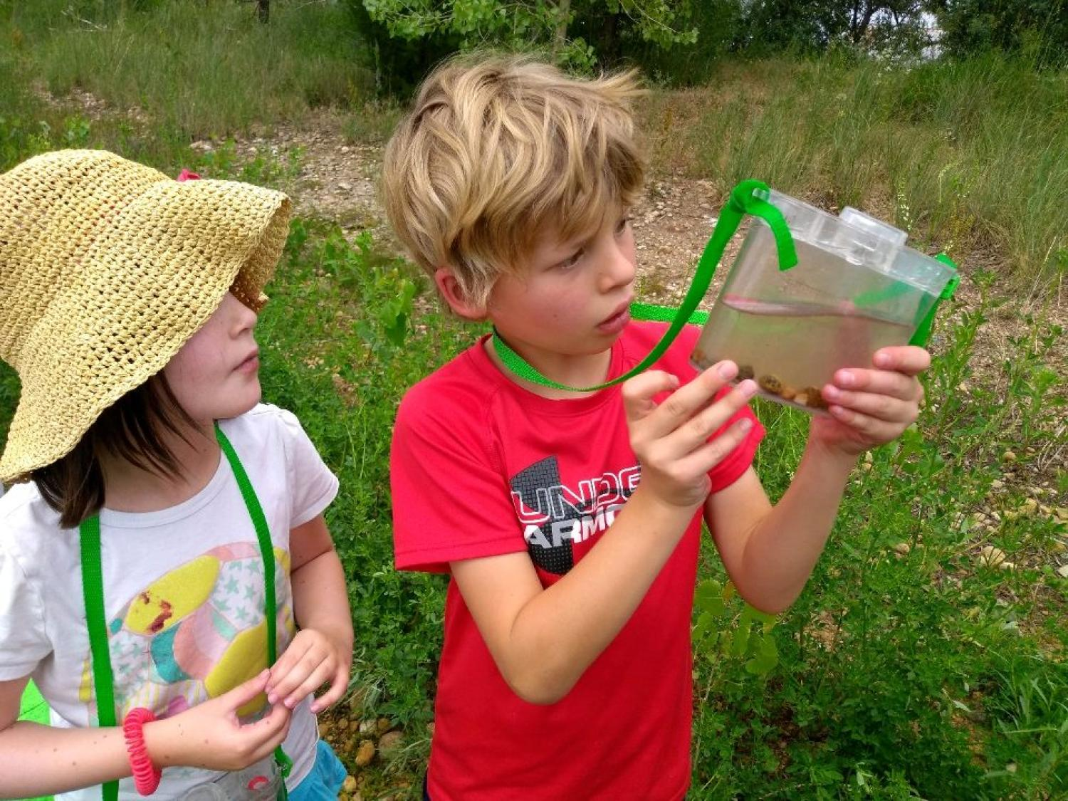 two kids overseeing the pond life they caught