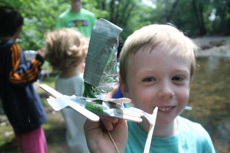 boy holding up craft