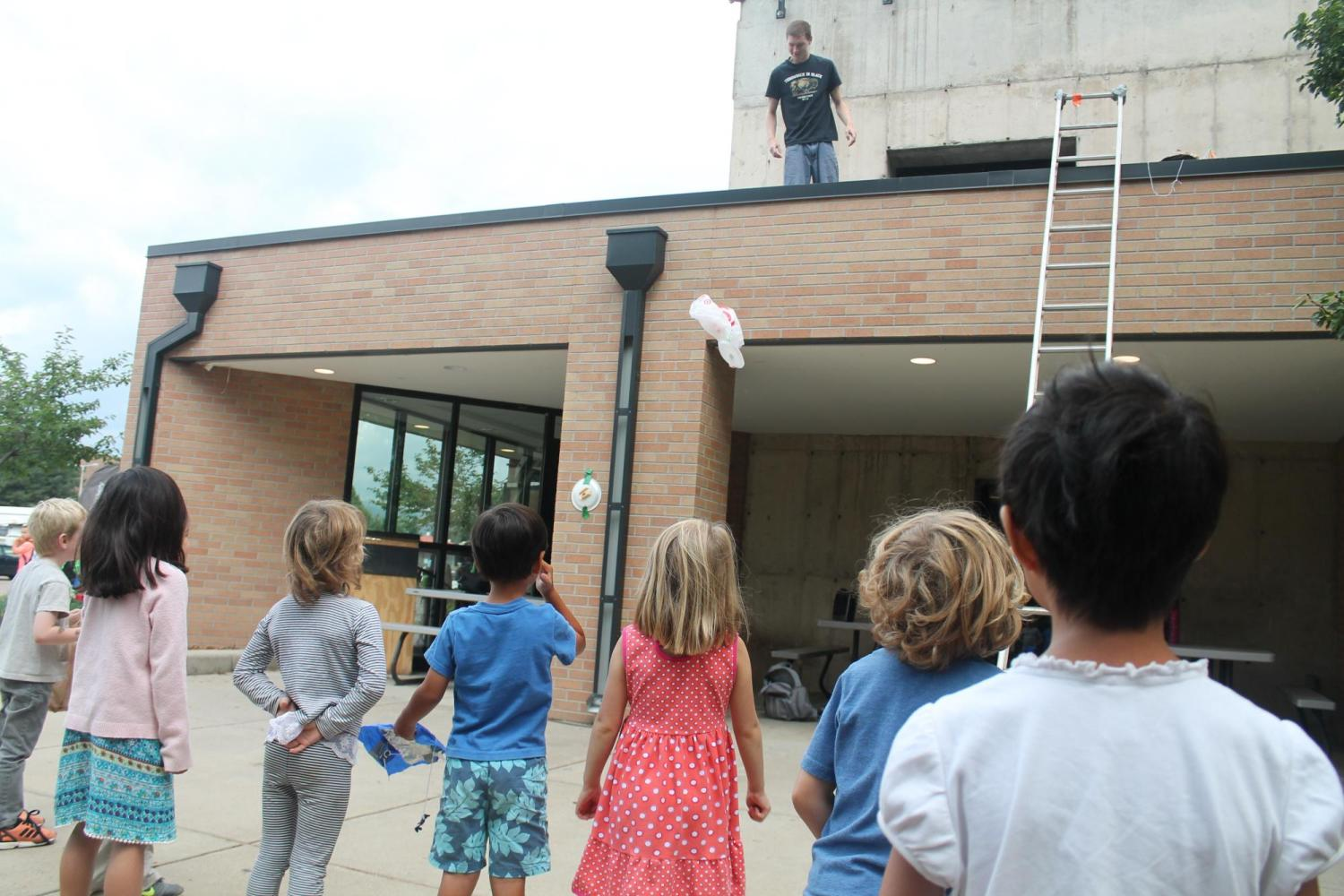 group of kids watching creations being launched from rooftop