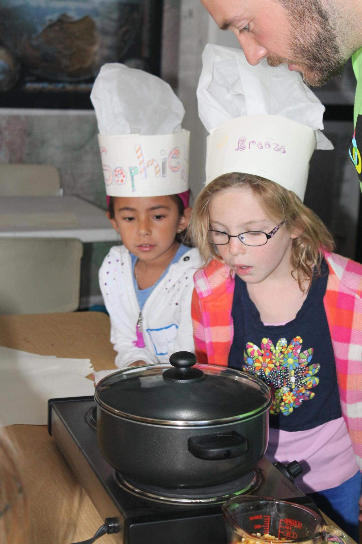 two girls in chef hats watching pot on burner