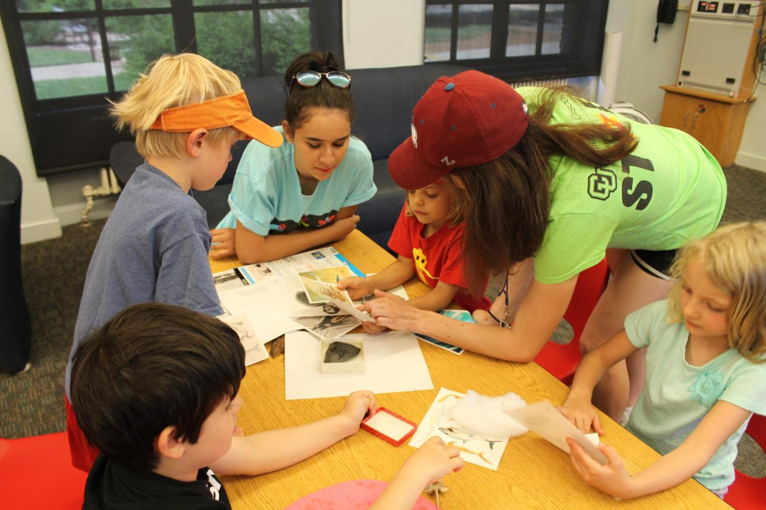 group of kids looking at specimens with teachers