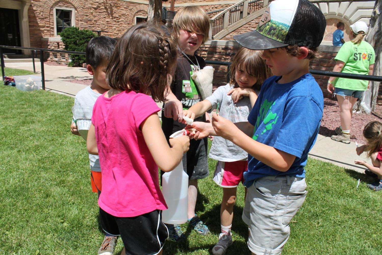 kids gathered together and excavating dinosaur bones