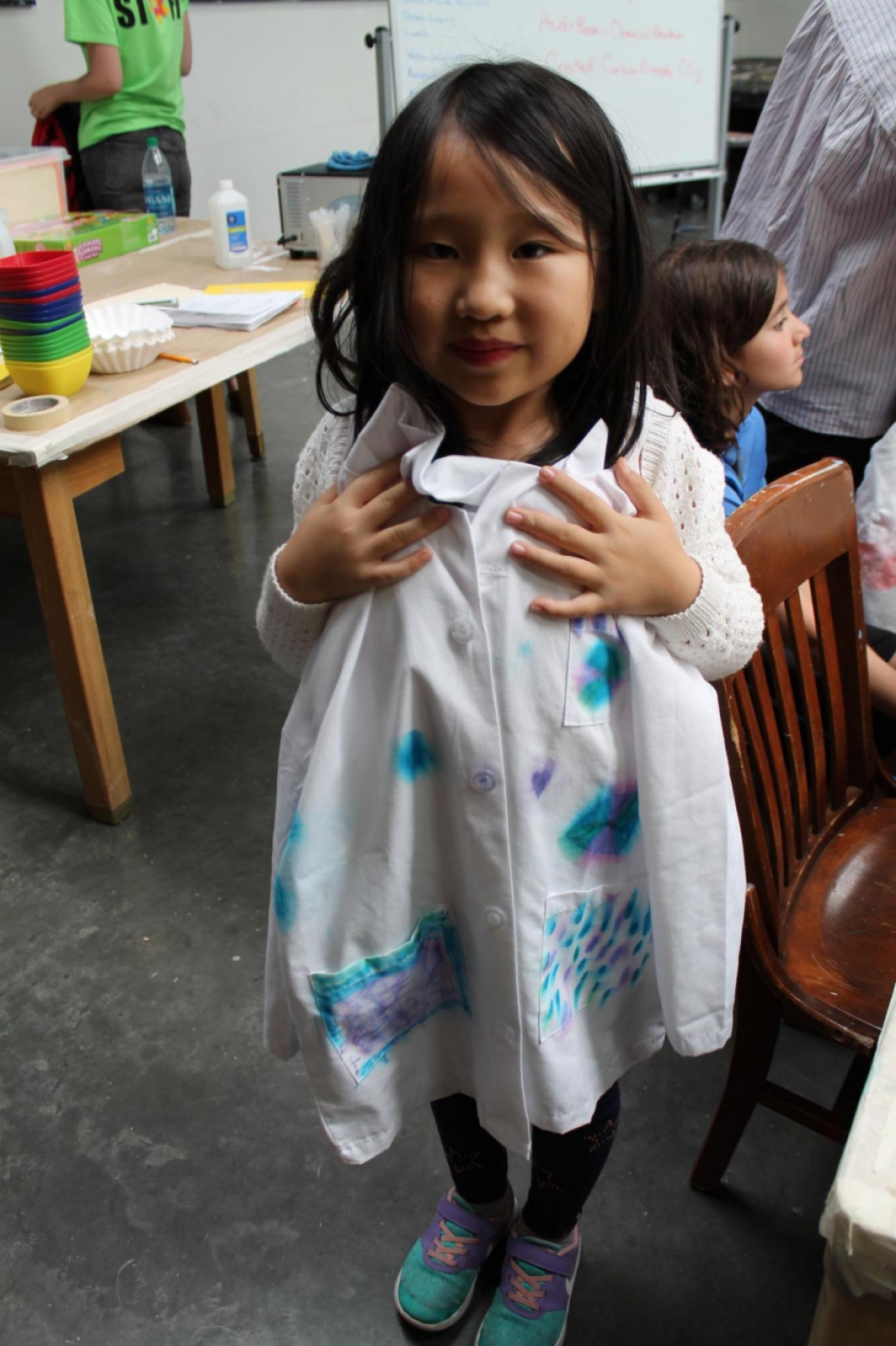 girl holding up hand painted lab coat