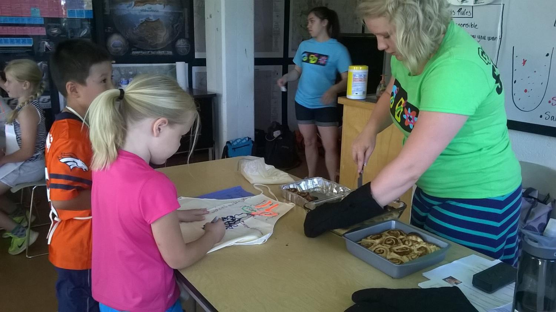 children helping teacher with cinnamon rolls