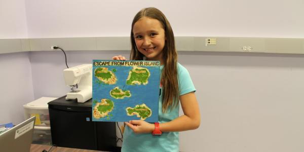 girl holding up her handmade board game