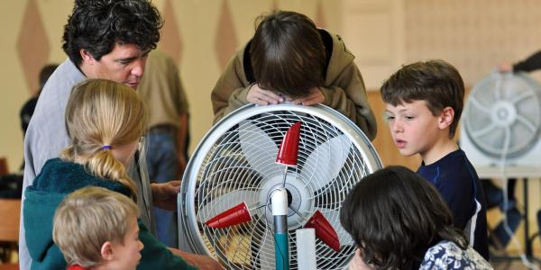 students and teacher working on project with a fan