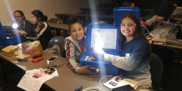 2 teens using a solar suitcase to illuminate a light bulb.