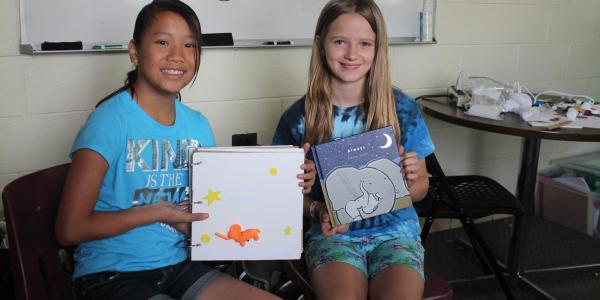 2 girls displaying their 3D printed book for low-vision and blind readers.