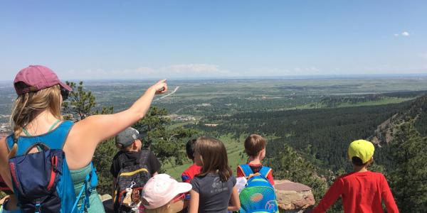An instructor is pointing out some geologic features in the landscape to student