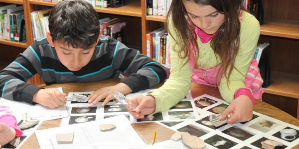 a boy and girl looking at archeological specimens