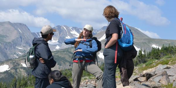 A group of Mountain Research Experience students talking with a researcher at a scenic overlook.