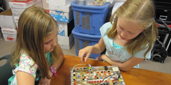 2 kids working on electronic board.