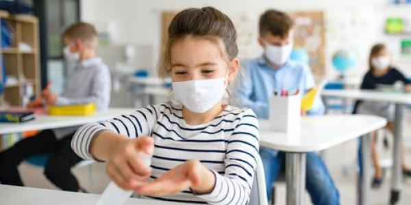 kid with mask on sanitizing hands