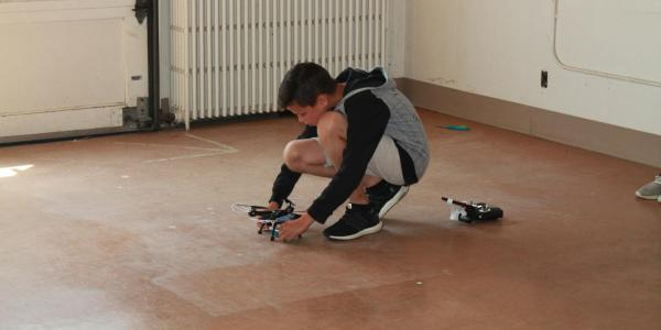 Boy bending down to adjust drone; controller is on the ground behind him.