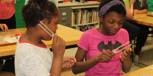 2 girls listening to sound waves on tuning forks.