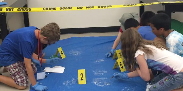 group of students analyzing a crime scene