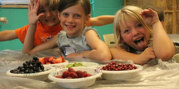 kids posing with bowls of fruit