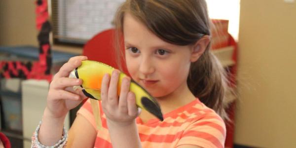 girl looking a bird beak replica