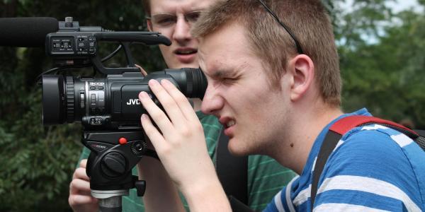 boy looking through video camera