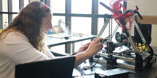 Teacher using a 3D printer.