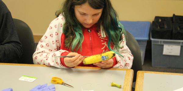 girl practicing sutures on a banana