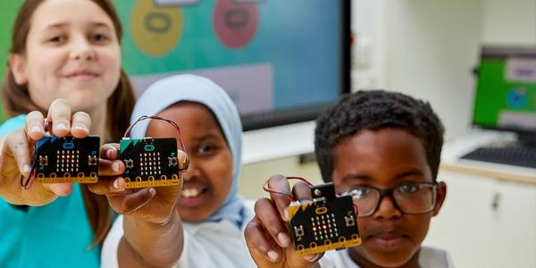 kids holding up microbit