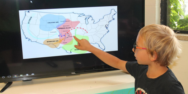 boy pointing at storms on a map