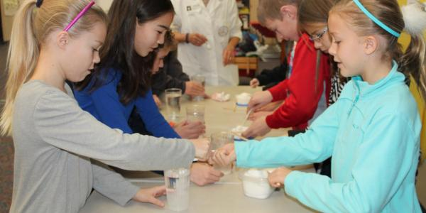 a group of kids doing a table top experiment