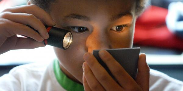 boy playing with laser and mirror