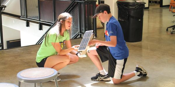 A camper and TA kneeling as they look at the construction of his solar car.