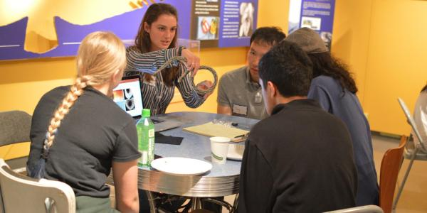 Several teens gathered to listen to a scientist at the museum.