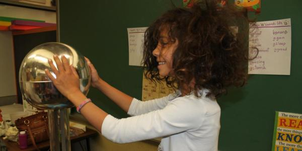 girl doing hair-raising experiment