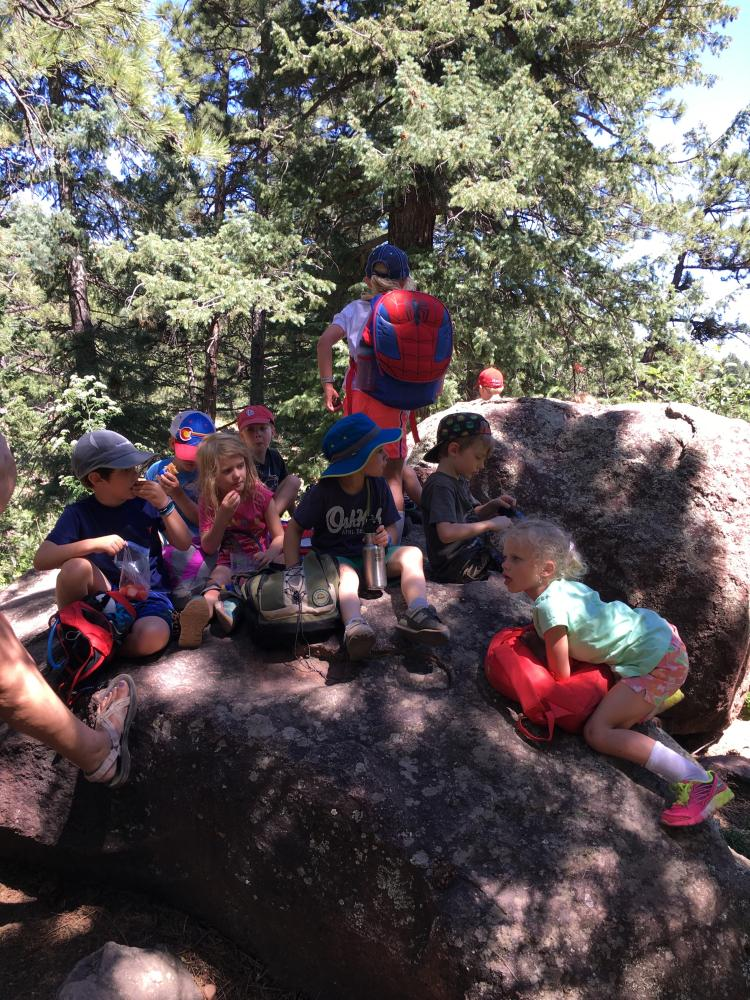 children sitting on a large rock