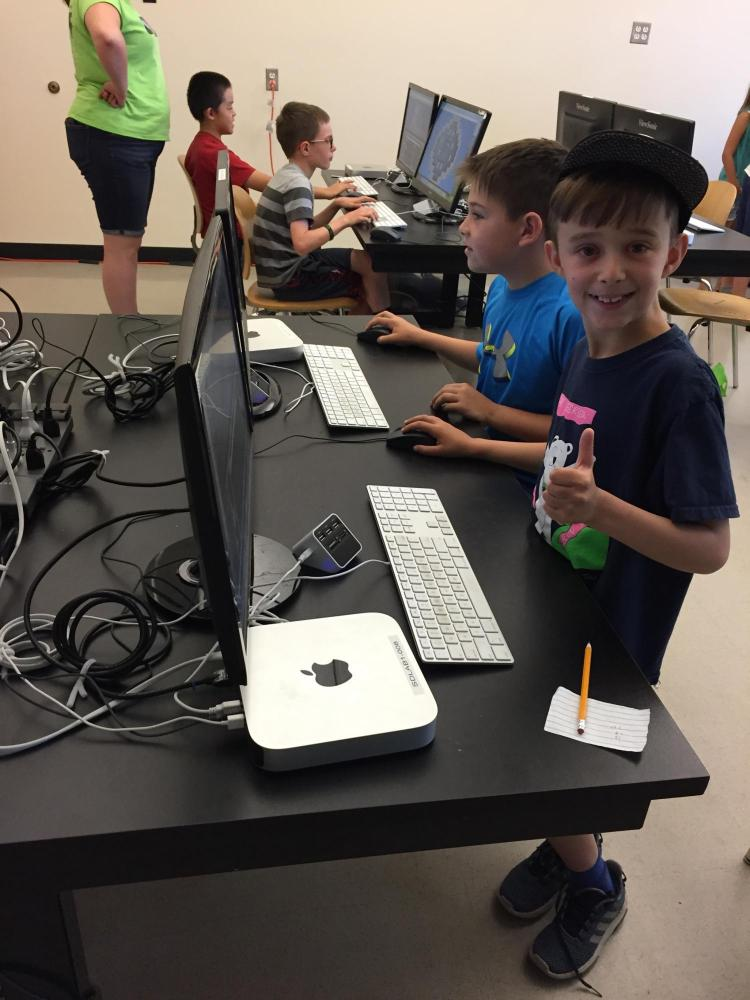 boy holding thumbs up in front of computer