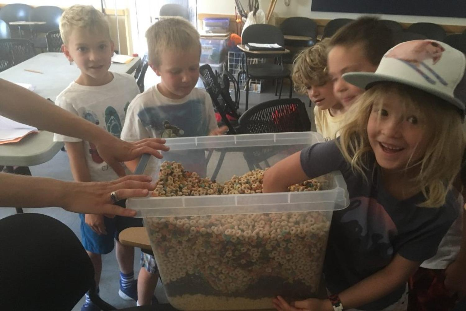 Children playing with bin of cereal