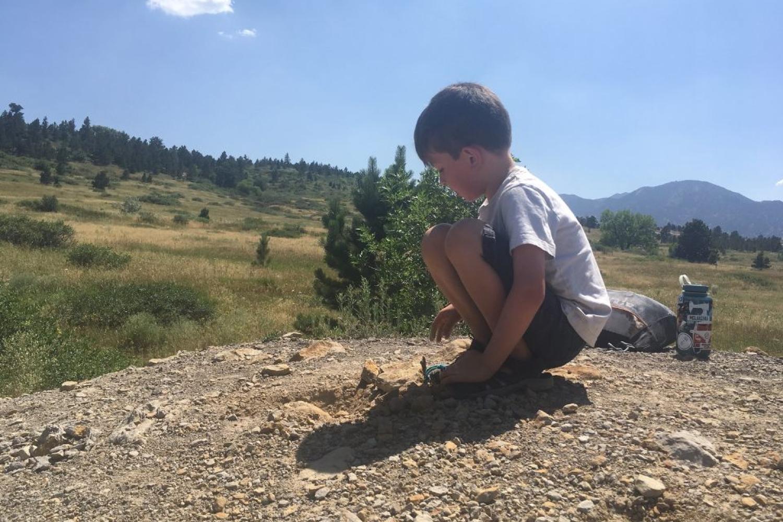 boy examining rocks on mountain