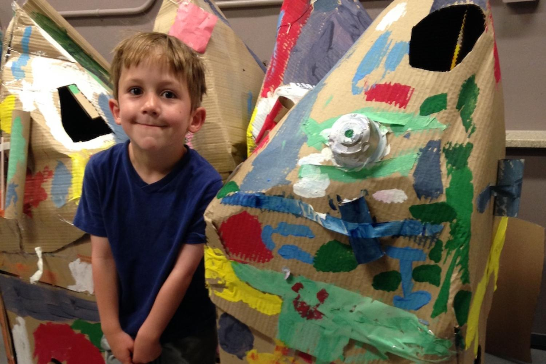 boy standing next to cardboard rocket