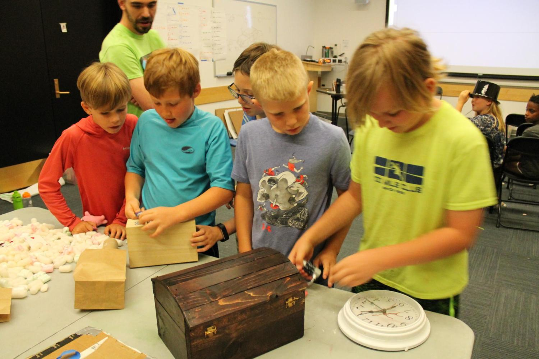 Group of boys unlocking a box