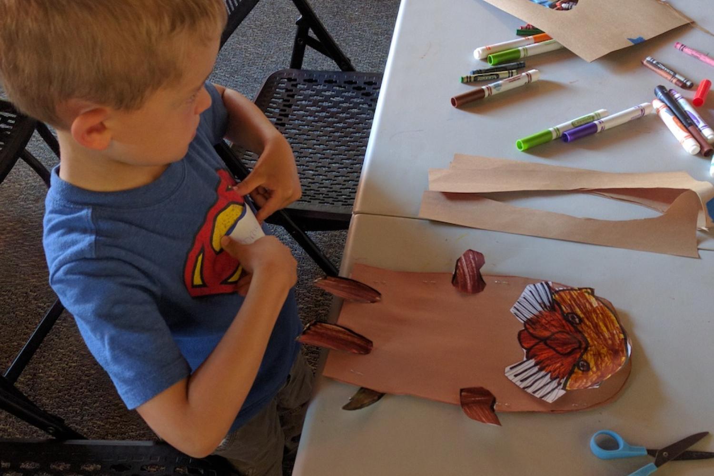 boy making paper otter craft