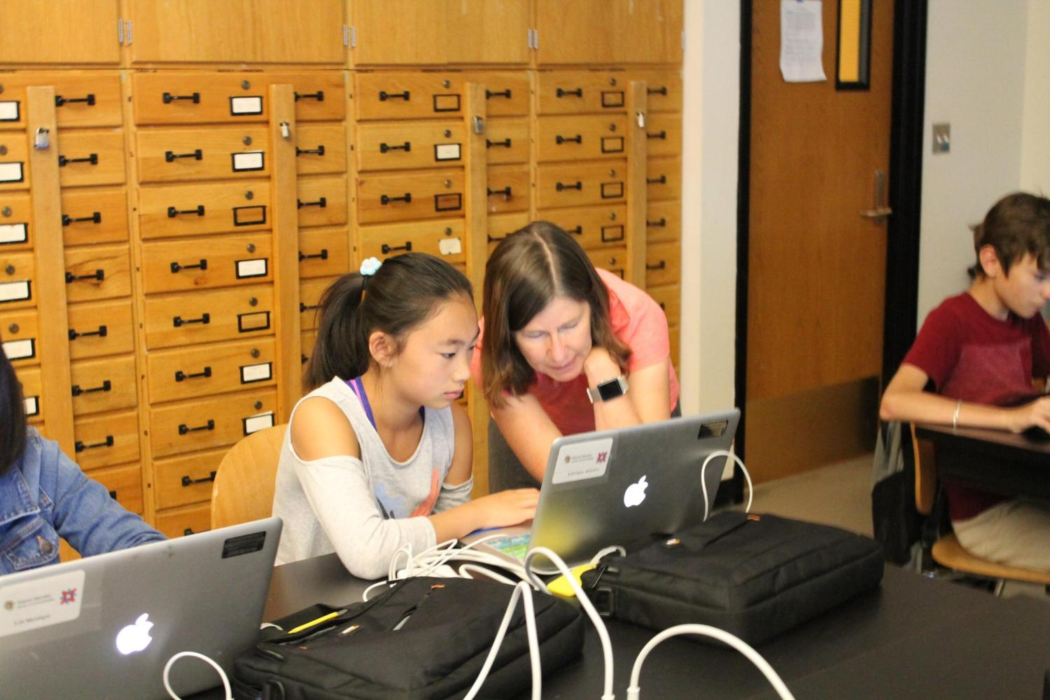 girl working with teacher at laptop