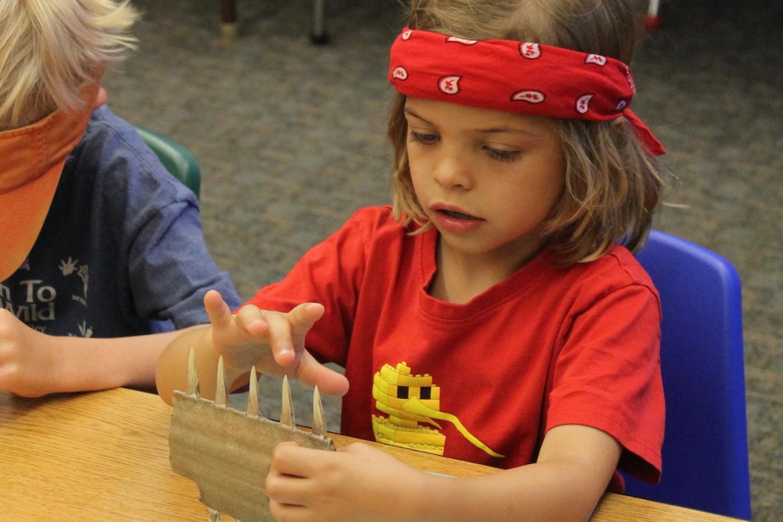 girl examining cardboard model