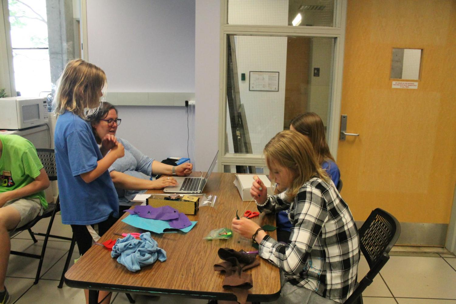 students with teacher at table, handsewing