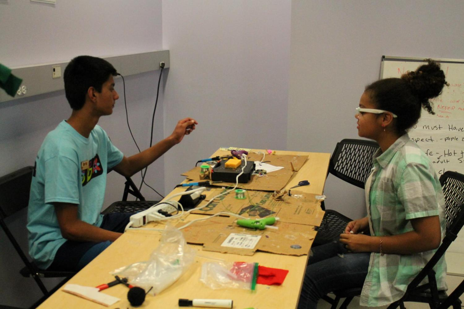 two students with electronics
