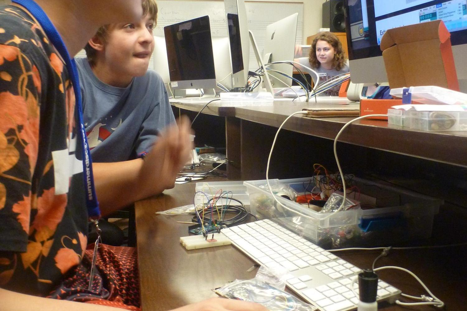 Student working on computer with arduino
