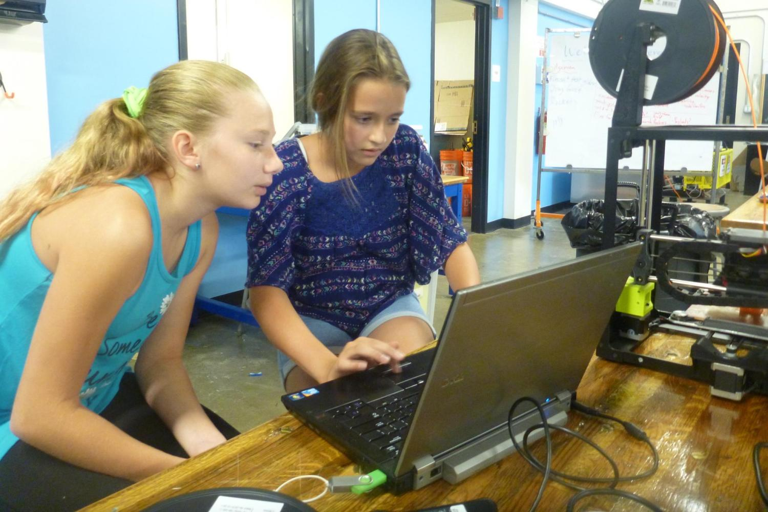 two girls working on laptop with 3D printer
