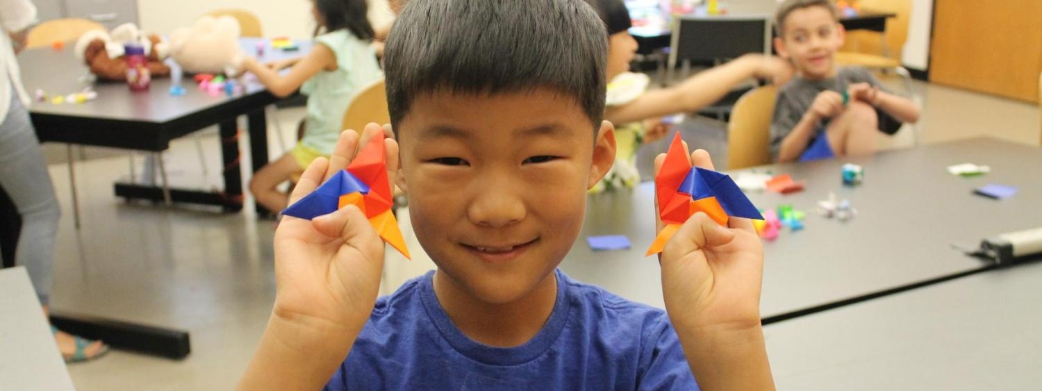 boy showing his origami project