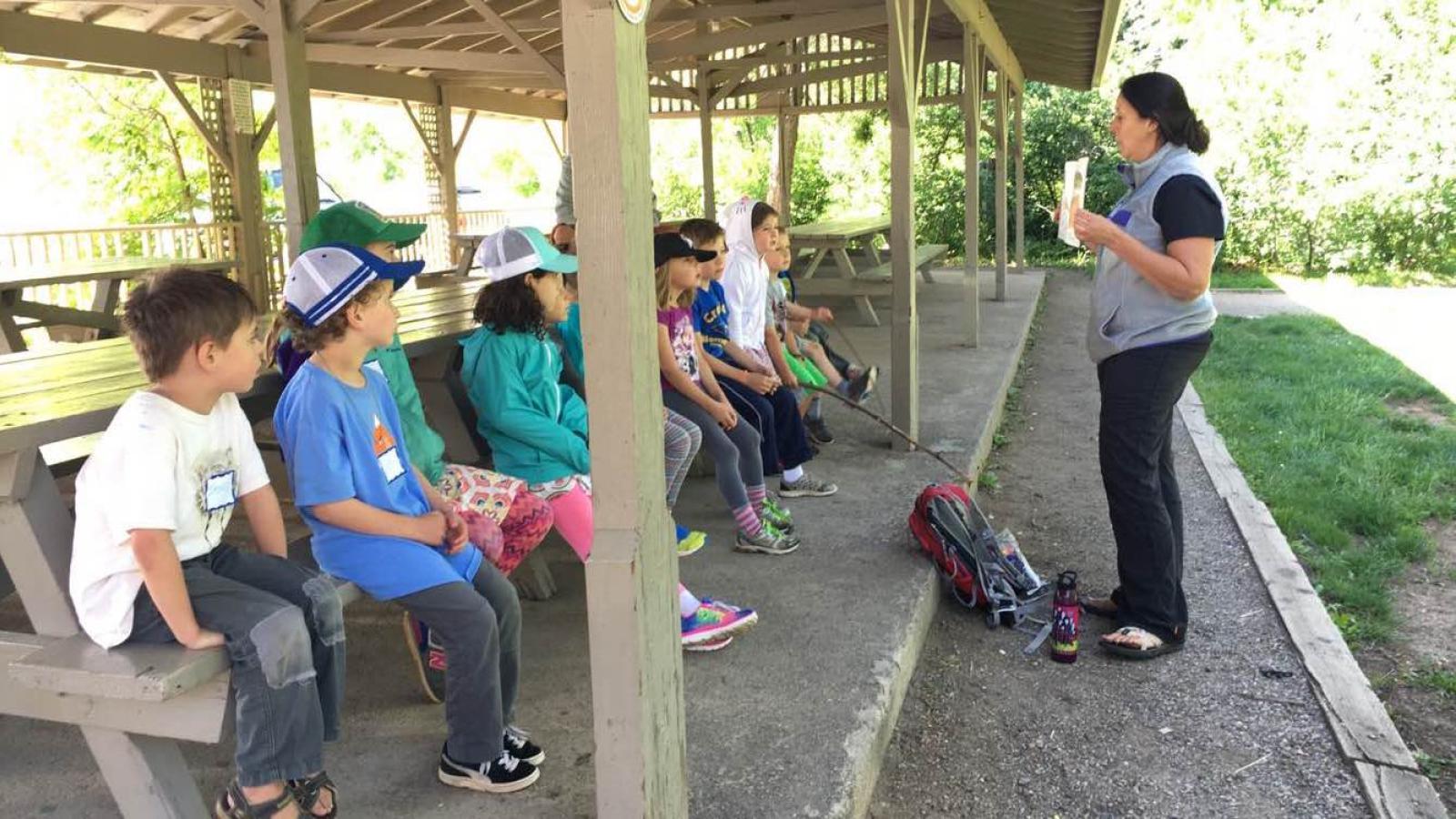 teacher reading kids a story outdoors