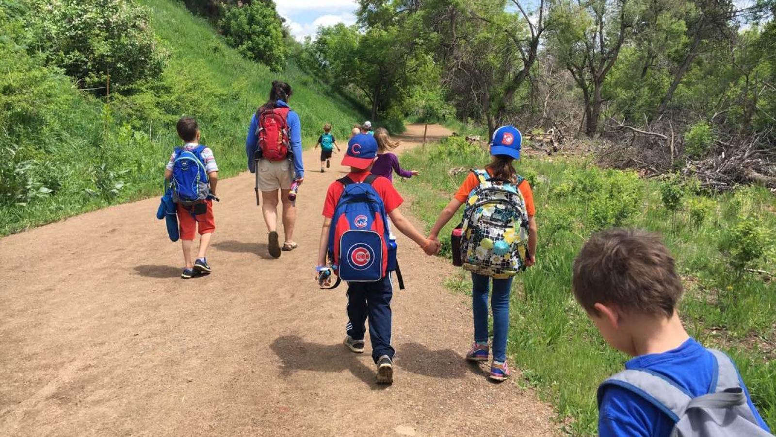 kids holding hands as they hike