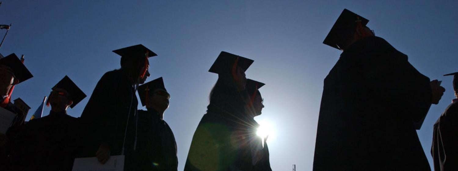 Silhouetted students at commencement