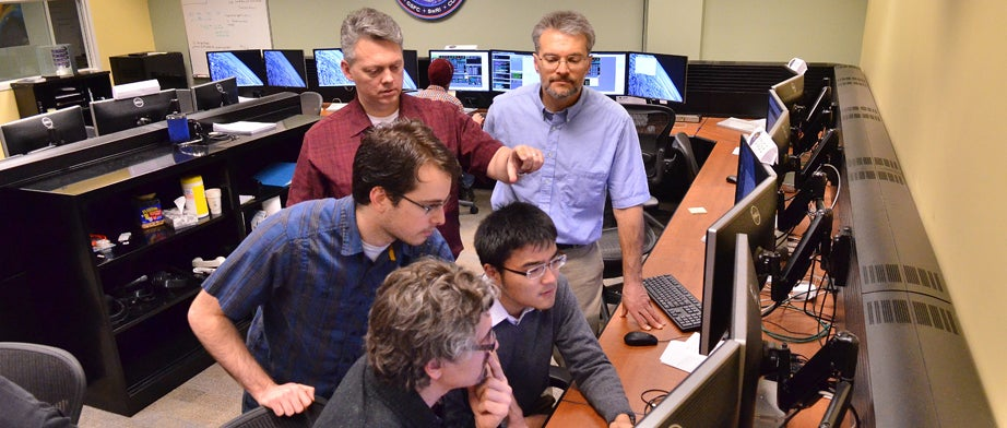 Group of engineers studying around a computer